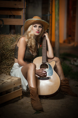 barn boots: Attractive woman with country look, indoors shot, american country style. Blonde girl with straw cowboy hat and guitar. Fair hair female with boots posing with a guitar sitting on straw bale in barn