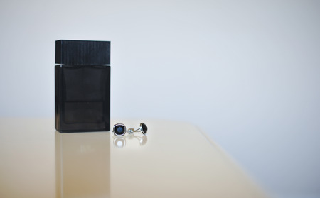 cufflinks: Black perfume bottle and silver cuff-links isolated on gray background. Wedding accessories. Stock Photo