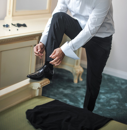 businesswear: Best man getting ready for a special day. A groom putting on shoes as he gets dressed in formal wear. Grooms suit