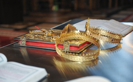 devotional: crosses , rings and crowns of gold on the table in church.Wedding celebration