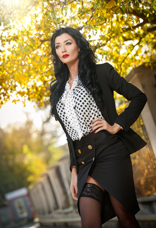 fade away: Attractive young woman in a autumnal fashion shot. Beautiful fashionable lady in black and white outfit posing provocatively in park. Elegant brunette in fall scenery on faded trees background . Stock Photo