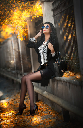 fade away: Attractive young woman with sunglasses in autumnal fashion shot. Beautiful lady in black and white outfit with short skirt sitting on wall in park. Elegant brunette in fall scenery with rusty leaves.