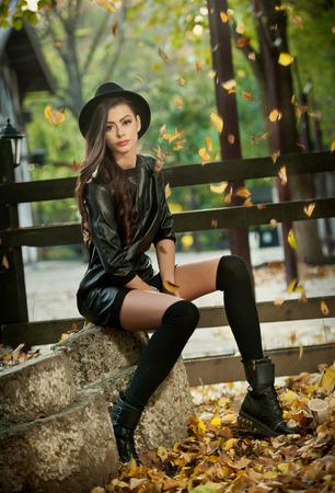 Attractive young woman in an autumnal shot, outdoors. Beautiful fashionable girl with modern outfit posing sitting in park. Elegant slim brunette with long legs, hat and short skirt in fall scenery. Stock Photo