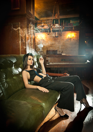 sensually: Young beautiful brunette woman in black male  trousers, hat and braces relaxing on a sofa in vintage scenery. Romantic mysterious young lady with black bra smoking sensually in luxurious interior.