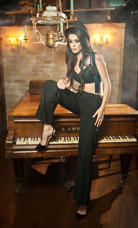femme brune sexy: belle jeune femme brune en pantalon noir m�le, chapeau et bretelles assis sur un piano dans un d�cor vintage. Romantique jeune femme myst�rieuse avec soutien-gorge noir posant sensuellement int�rieur luxueux.