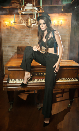 bra model: Young beautiful brunette woman in black male trousers, hat and braces sitting on a piano in vintage scenery. Romantic mysterious young lady with black bra posing sensually in luxurious interior.
