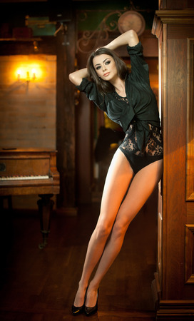 tight fit: Young beautiful brunette woman in black tight fit body posing sensual in vintage scenery. Romantic mysterious young lady with long legs in luxurious interior. Sensual girl standing near wooden wall Stock Photo