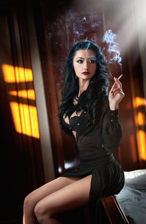 Young beautiful brunette woman in black dress relaxing on the in vintage scenery. Romantic mysterious young lady holding sensually a cigarette, boudoir shot. Dark hair female smoking in bedroom