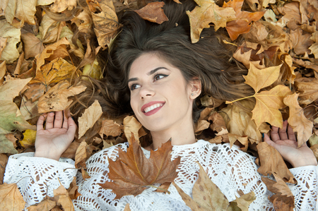woman laying down: Nice girl covered with autumnal leaves. Young woman laying down on the ground covered by fall foliage in park. Beautiful sexy girl lying on autumn leaves. Young woman covered with golden autumn leaves