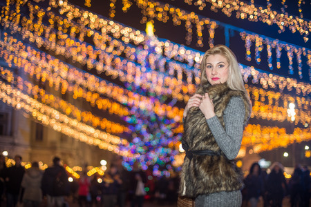 fun background: Portrait of young beautiful woman with long fair hair outdoor in cold winter evening. Beautiful blonde girl in winter clothes with xmas lights in background. Beautiful woman smiling in winter scenery Stock Photo