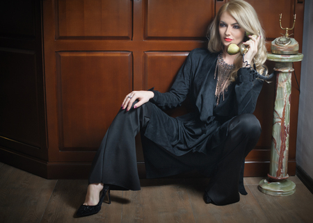 glamour model: Young beautiful blonde woman in elegant black suit talking by phone sitting relaxed on the floor. Seductive fair hair girl leaning on wooden cabinet holding a vintage phone in classic interior