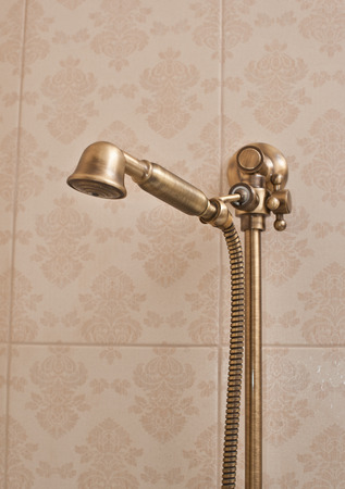 faience: Golden shower head on wall with faience. Vintage shower head