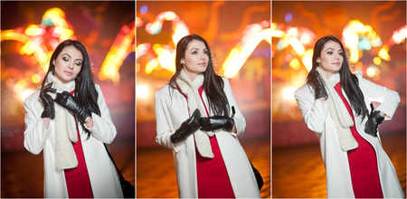 street shot: Fashionable lady wearing red dress and white coat outdoor in urban scenery with city lights in background. Full length portrait of young beautiful elegant woman posing in winter style. Street shot.