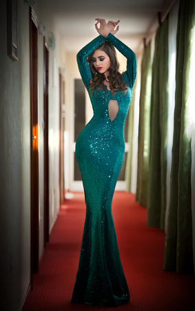 tight fit: Young beautiful luxurious woman in long elegant turquoise dress posing indoors. Attractive brunette with tight fit glamorous dress in hotel lobby. Fashionable seductive female on red carpet of hall