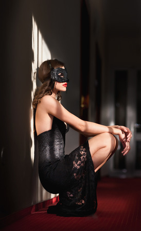 Portrait of attractive sensual young woman with mask, indoors. Sexy brunette lady posing provocatively sitting on the floor. Beautiful long hair girl with red lips and short lace dress, boudoir shot
