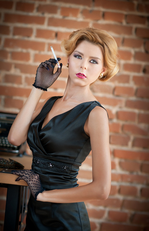 short gloves: Young beautiful short hair blonde woman in black dress smoking a cigarette. Elegant romantic mysterious lady with movie star look, red bricks wall on background. Retro style blonde with gloves Stock Photo