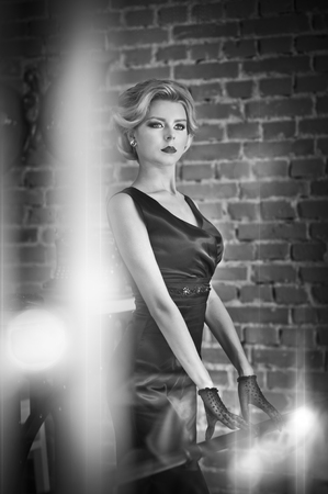 short gloves: Young beautiful short hair blonde woman in black dress posing, black and white photo. Elegant romantic mysterious lady with movie star look, bricks wall on background. Retro style blonde with gloves