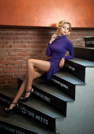Young beautiful short hair blonde woman in mauve turtle neck tight short dress sitting on stairs. Romantic mysterious lady with movie star retro look posing provocatively, red bricks wall background Stock Photo