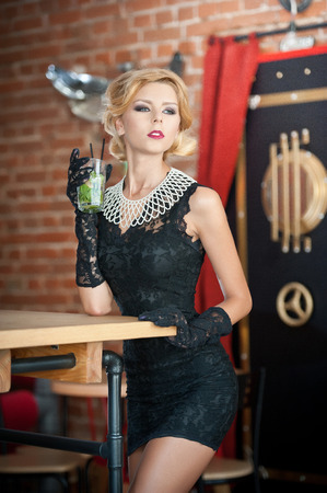 cute girl: Fashionable attractive lady with little black dress and long gloves standing near a restaurant table having a drink. Short hair blonde woman with makeup and creative haircut holding a glass with fresh