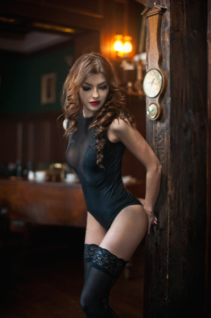 Young beautiful brunette woman in black tight fit corset posing sensual in vintage scenery. Romantic mysterious young lady with long legs in luxurious interior. Sensual girl standing near wooden wall Standard-Bild