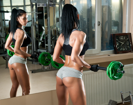 reflection: Gorgeous brunette working on her muscles in a gym, mirror reflection. Fitness woman doing workout. Sporty girl doing exercise in fitness center. Beautiful brunette toning her muscles at the gym