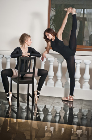 tight fit: Two graceful ballerinas, one doing the splits and one sitting on chair, on the marble floor. Gorgeous ballet dancers, brunette and blonde, in black tight fit ballet outfits making their exercises.