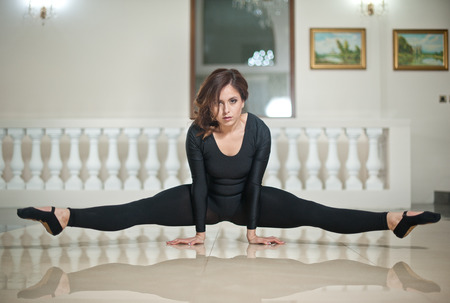 tight fit: Graceful ballerina doing the splits on the marble floor. Gorgeous ballet dancer performing a split on glossy floor. Short hair young brunette in tight fit ballet outfit making her exercises. Stock Photo