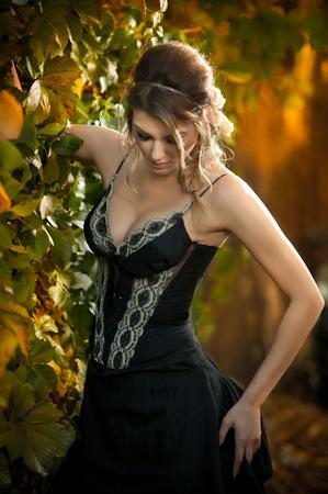 voluptuosa: Hermosa mujer sensual con rosas en el pelo que presenta cerca de una pared de hojas verdes. Hembra joven en negro elegante vestido de so�ar despierto en la naturaleza. Se�ora atractiva voluptuosa con el arreglo de cabello creativo Foto de archivo