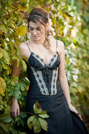 voluptuous: Hermosa mujer sensual con rosas en el pelo que presenta cerca de una pared de hojas verdes. Hembra joven en negro elegante vestido de so�ar despierto en la naturaleza. Se�ora atractiva voluptuosa con el arreglo de cabello creativo Foto de archivo