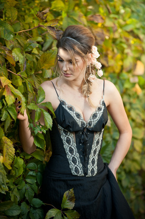 Beautiful sensual woman with roses in hair posing near a wall of green leaves. Young female in black elegant dress daydreaming in nature. Attractive voluptuous lady with creative hair arrangement Stock Photo