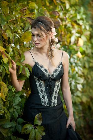 voluptuosa: Hermosa mujer sensual con rosas en el pelo que presenta cerca de una pared de hojas verdes. Hembra joven en negro elegante vestido de soñar despierto en la naturaleza. Señora atractiva voluptuosa con el arreglo de cabello creativo Foto de archivo