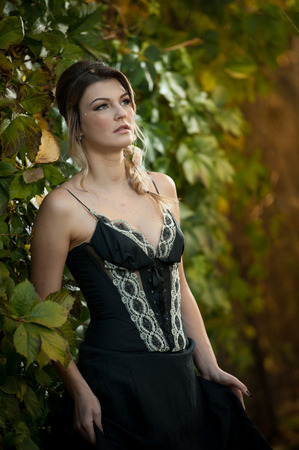 voluptuous: Beautiful sensual woman with roses in hair posing near a wall of green leaves. Young female in black elegant dress daydreaming in nature. Attractive voluptuous lady with creative hair arrangement Stock Photo