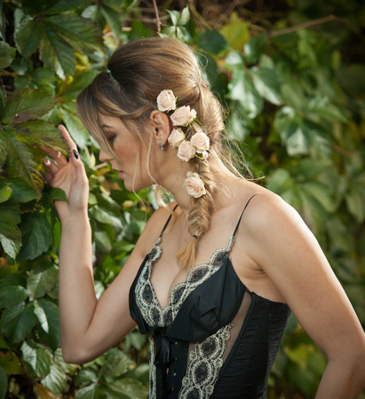 decolletage: Beautiful sensual woman with roses in hair posing near a wall of green leaves. Young female in black elegant dress daydreaming in nature. Attractive voluptuous lady with creative hair arrangement Stock Photo