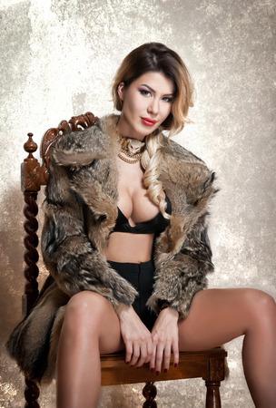 manteau de fourrure: Jolie femme blonde et sexy avec lingerie noire et manteau de fourrure pose provocante assis sur une chaise, fond gris. Femme sensuelle avec des cheveux blonds et belles jambes regarder la caméra