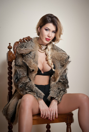 Attractive and sexy blonde woman with black lingerie and fur coat posing provocatively sitting on chair, gray background. Sensual female with fair hair and beautiful legs looking into the camera Stock Photo