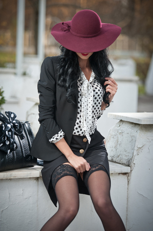 Attractive young woman with burgundy colored large hat in autumnal fashion shot. Beautiful lady in black outfit with short skirt and sexy stockings sitting on marble wall. Elegant brunette outdoors.