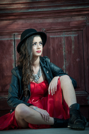 seductive women: Young beautiful brunette woman with red short dress and black hat posing sensual in vintage scenery. Romantic mysterious young lady relaxing sitting on floor against vintage wooden wall Stock Photo
