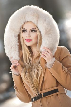 Attraktive junge kaukasischen erwachsenen mit hellbraunen Pelzmantel Kapuze. Schöne blonde Mädchen mit wunderschönen Augen das Tragen von Pelz, Aussenaufnahme. Makeup - sinnlich langen blonden Haaren weibliche Art Porträt, Wintersaison
