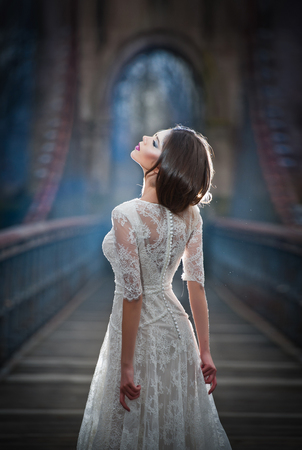 Lovely young lady wearing elegant white dress enjoying the beams of celestial light and snowflakes falling on her face. Pretty brunette girl in long wedding dress posing on a bridge in winter scenery Stock fotó