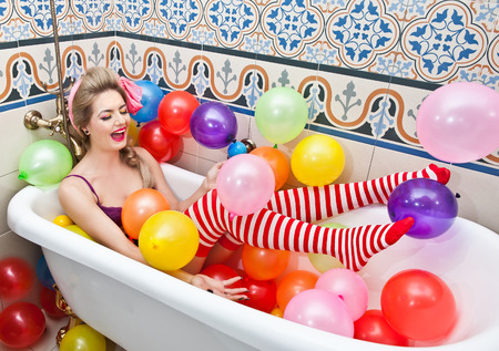 Blonde woman playing in her bath tube with bright colored balloons. Sensual girl with white and red striped stockings having fun in bathroom, covered with balloons Standard-Bild