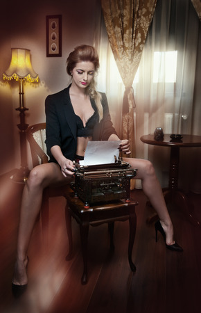 Attractive sexy blonde woman with black bra posing provocatively sitting on chair typing on typewriter. Beautiful woman with long legs on high heels wearing black jacket over lingerie in vintage room Stock Photo