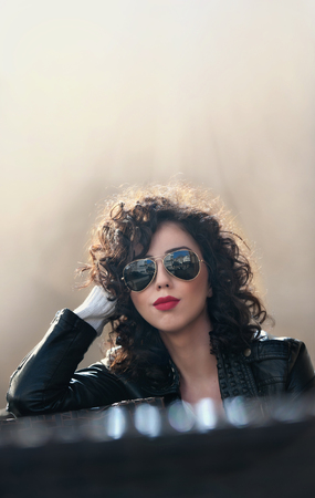 mujeres elegantes: mujer morena encantadora joven rizado con gafas de sol y chaqueta de cuero negro contra la pared. mujer joven magnífica atractiva con aspecto moderno. Retrato de la muchacha sensual con la boca voluptuosa Foto de archivo