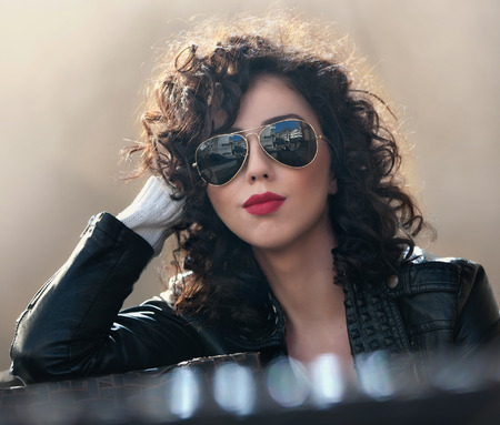 cute attitude: Charming young curly brunette woman with sunglasses and black leather jacket against wall. Sexy gorgeous young woman with modern look. Portrait of sensual girl with voluptuous mouth