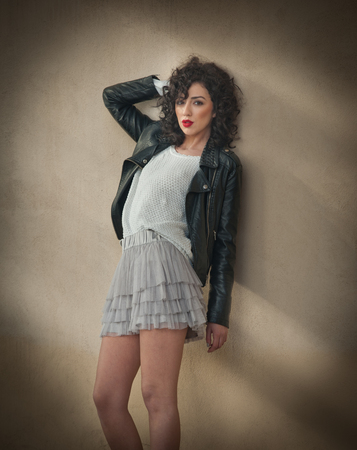 leather skirt: Charming young curly brunette woman in lace short skirt and black leather jacket leaning against a wall. Sexy gorgeous young woman with long legs near wall. Full length portrait of sensual girl posing