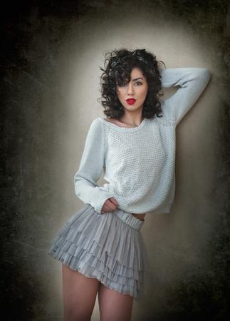 voluptuosa: mujer morena encantadora joven rizada en encaje falda corta y una blusa blanca que se inclina contra la pared. mujer joven magnífica atractiva con las piernas largas cerca de la pared. Retrato de la muchacha sensual con la boca voluptuosa posando