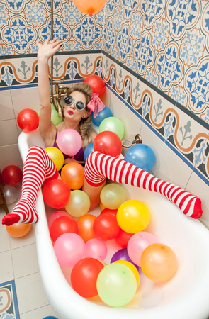 Blonde woman with sunglasses playing in her bath tube with bright colored balloons. Sensual girl with white and red striped stockings having fun in bathroom, covered with balloons