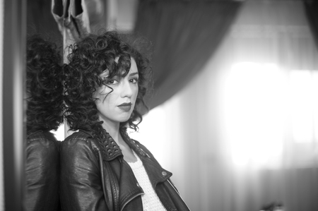 voluptuosa: mujer morena encantadora joven rizada con chaqueta de cuero negro. mujer joven magnífica atractiva con aspecto moderno. Retrato de la muchacha sensual con la boca voluptuosa sensación interior tristes, blanco y negro tiro