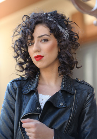 voluptuous: Charming young curly brunette woman with black leather jacket. Sexy gorgeous young woman with modern look. Portrait of sensual girl with voluptuous mouth wearing bright red lipstick, outdoor shot Stock Photo