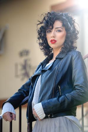 voluptuous: mujer morena encantadora joven rizada con chaqueta de cuero negro. mujer joven magn�fica atractiva con aspecto moderno. Retrato de la muchacha sensual con la boca voluptuosa usando una falda tut� gris, dispararon al aire libre