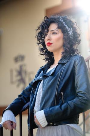 voluptuosa: mujer morena encantadora joven rizada con chaqueta de cuero negro. mujer joven magnífica atractiva con aspecto moderno. Retrato de la muchacha sensual con la boca voluptuosa usando una falda tutú gris, dispararon al aire libre